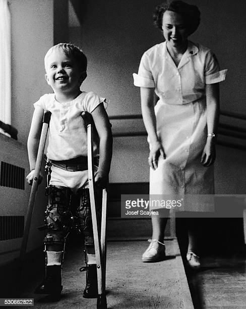 Nurse watches as a young boy recovering from polio walks with crutches and leg braces at the Children's Hospital of Seattle.
