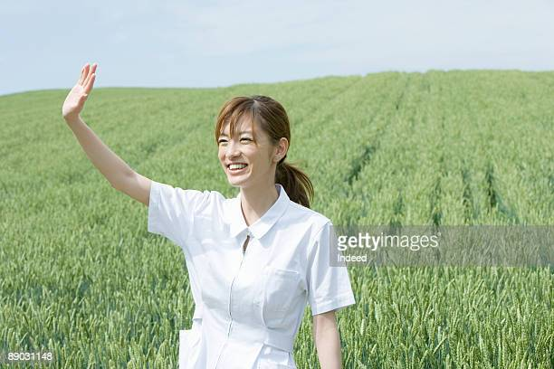 nurse waving in a field of tall grass - 手を振る ストックフォトと画像