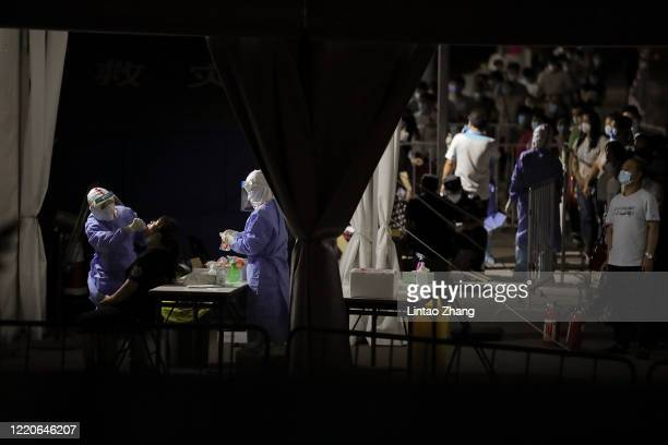 A nurse wearing a protective suit and mask takes a nucleic acid test for COVID19 from a person who either visited or lives near the Xinfadi Market at...