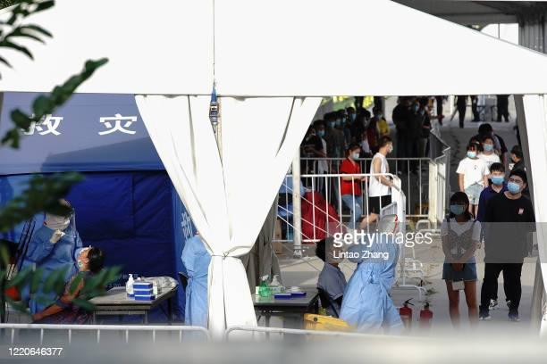 Nurse wearing a protective suit and mask takes a nucleic acid test for COVID19 from a person who either visited or lives near the Xinfadi Market at a...