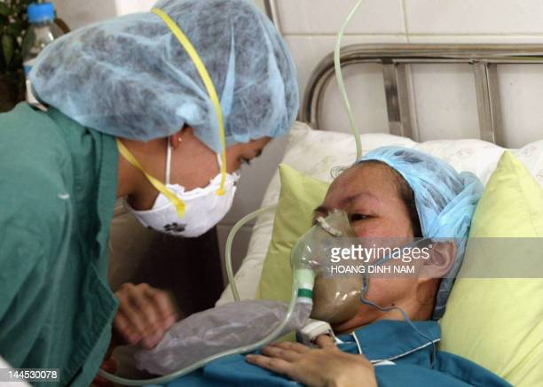 A nurse wearing a surgical mask listens to a SARS patient at the institute of tropical diseases at Hanoi's Bach Mai hospital 07 April 2003 Vietnamese...