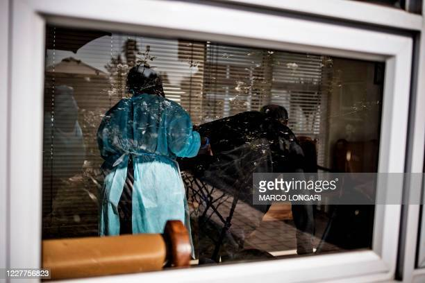 Nurse wearing personal protective equipment assists a man, a resident of Casa Serena, an Old Age home in Johannesburg, on July 22, 2020. - Senior...
