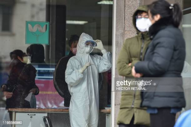 A nurse wearing protective clothing to help stop the spread of a deadly virus which began in the city looks at a thermometer at the Wuhan Fifth...