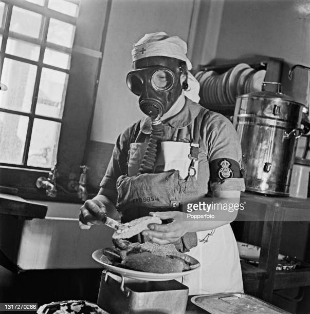 Nurse wears a gas mask respirator as she prepares food in the kitchens at Shenley Hospital, a military hospital at Shenley near St Albans in...