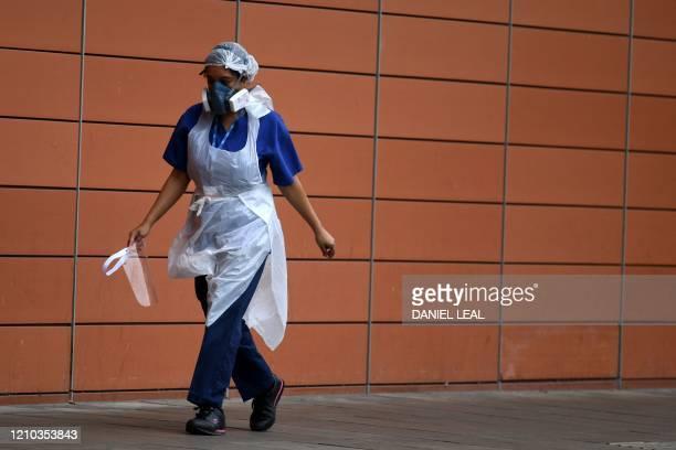 Nurse wears a protective face mask as she walks outside The Royal London Hospital in east London on April 18 during the novel coronavirus COVID-19...
