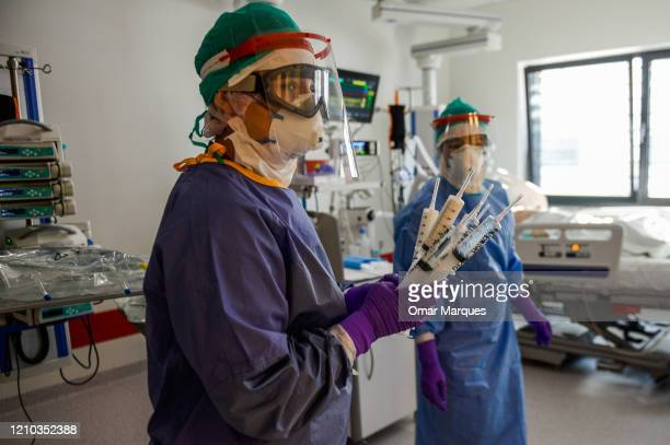 Nurse wears a protective, suit, mask, goggles and gloves as she carries syringes inside the Intensive Care Unit for COVID -19 patients of Krakow's...