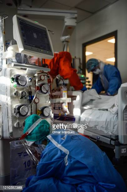 A nurse wears a protective suit mask goggles and gloves as she operates medical equipment inside the Intensive Care Unit for COVID 19 patients of...