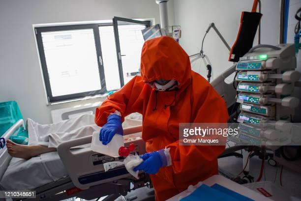 A nurse wears a protective suit mask goggles and gloves as she performs the morning medical check inside the Intensive Care Unit for COVID19 patients...