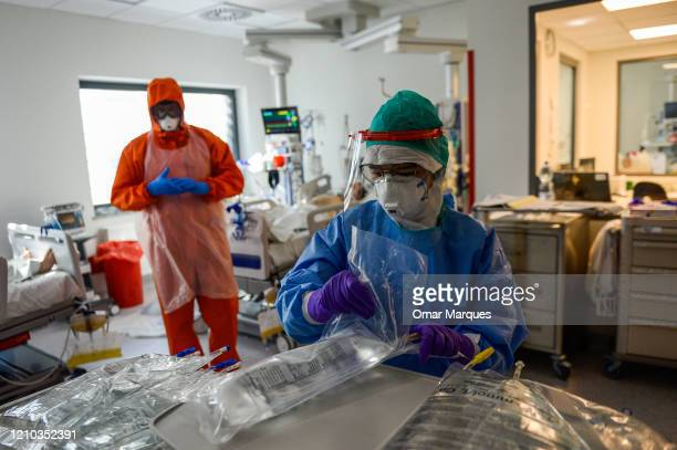 A nurse wears a protective suit mask goggles and gloves as she prepares medical remedies inside the Intensive Care Unit for COVID 19 patients of...