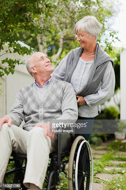 nurse wheeling older patient outdoors - 50 59 years stock pictures, royalty-free photos & images