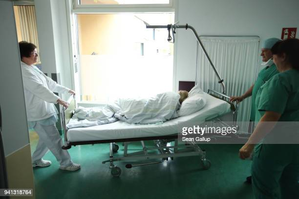 A nurse whhels away a young woman from Poland awaking from anesthesia as Dr Janusz Rudzinski looks on after the young woman underwent an abortion at...