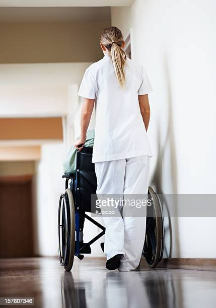 Nurse with a patient sitting in wheelchair at hospital corridor
