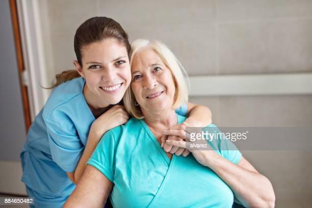Infirmière avec bras autour femme senior à l'hôpital