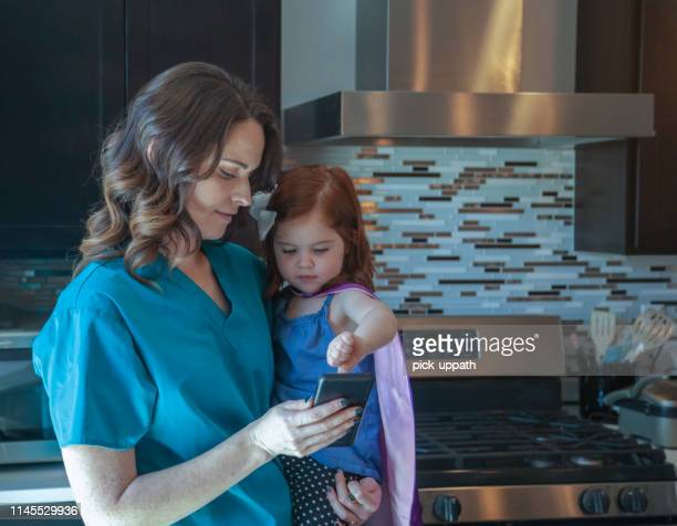 nurse with daughter in a cape playing with the phone - cute nurses stock pictures, royalty-free photos & images