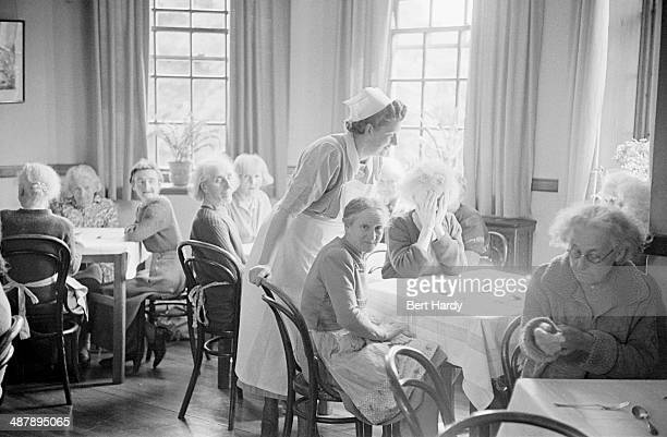A nurse with elderly patients in a day room at the Netherne Mental Hospital near Coulsdon Surrey 1953 Original publication Picture Post 6406 Mental...