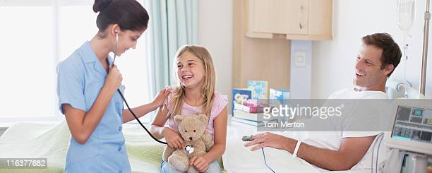 Nurse with father and daughter in hospital