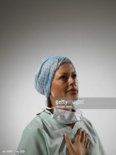 nurse with hand to heart - geschworener stock-fotos und bilder