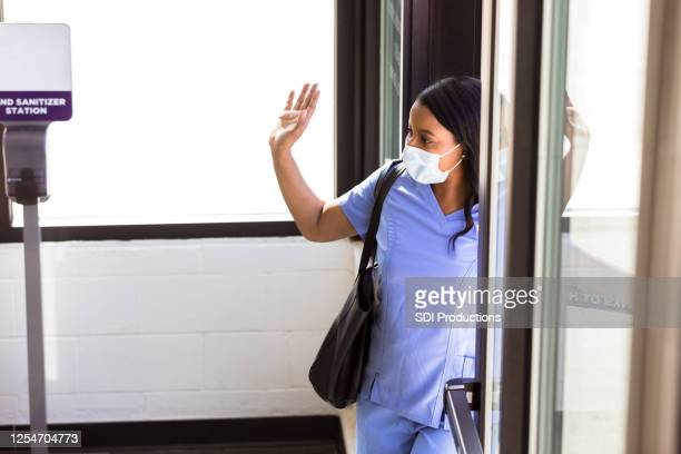 nurse with mask waves goodbye to co-workers - leaving stock pictures, royalty-free photos & images