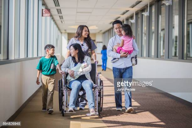 Nurse with patient and family in hospital hallway
