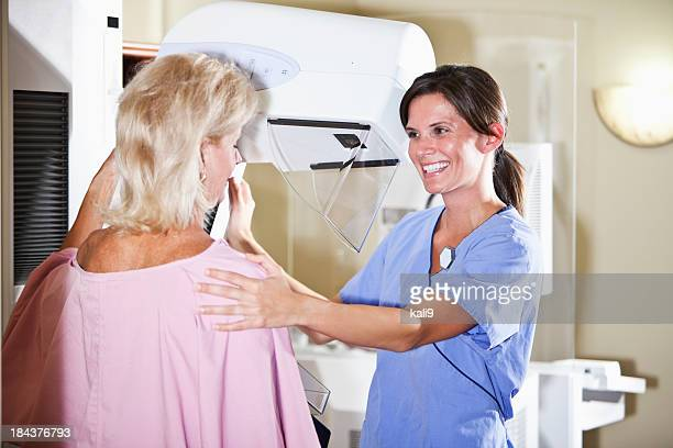 nurse with patient getting mammogram - mammogram stock pictures, royalty-free photos & images