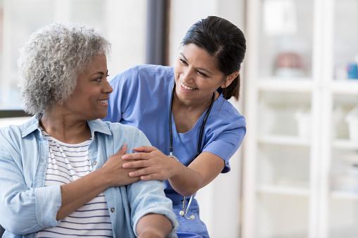 Nurse with senior patient 1055095174