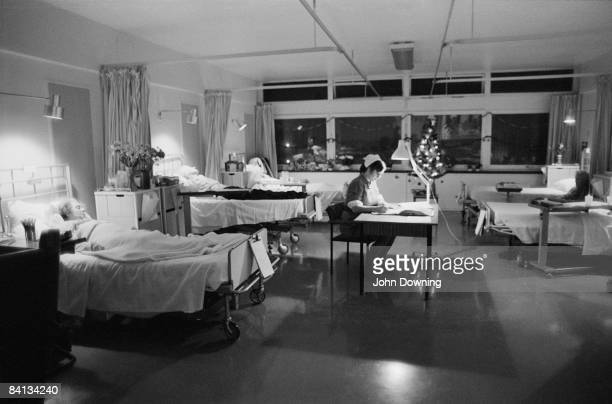 A nurse works the night shift in a hospital ward at Christmas December 1984