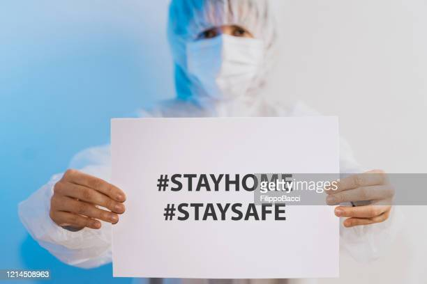 nurse/doctor holding a paper with a message for people to stay at home - illness prevention stock pictures, royalty-free photos & images