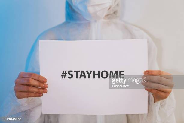 nurse/doctor holding a paper with a message for people to stay at home - aplanar a curva imagens e fotografias de stock