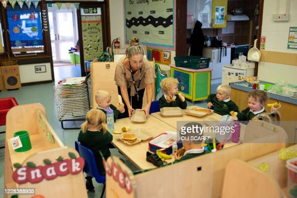 Nursery children have their lunch at their desks at Woodlands Primary Academy in Oldham, northern England on September 7, 2020. - Millions of...