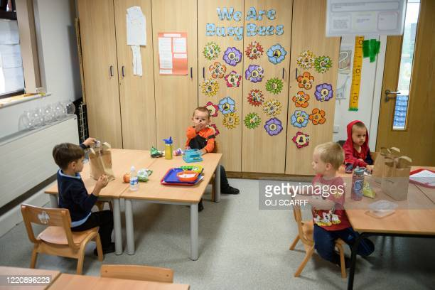 Nursery children have their lunch whilst sitting apart in order to minimise the risk of passing on Coronavirus at Willowpark Primary Academy in...