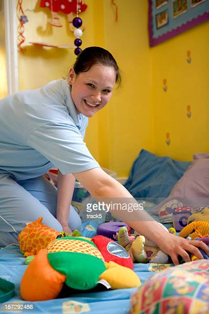 Nursery nurse (nanny) happily tidying her childrens toys