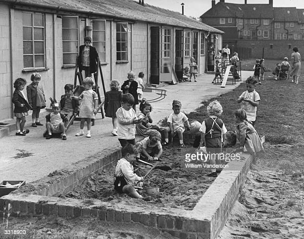 Nursery school children playing in a sand pit.