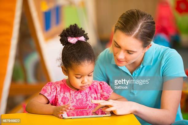 Nursery Teacher and Child using Digital Tablet