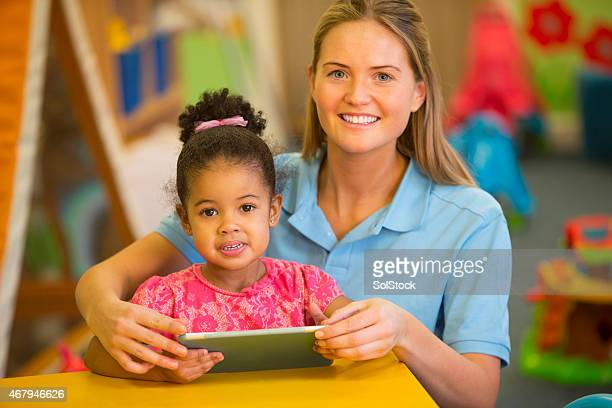 Nursery Teacher and Child using Digital Tablet