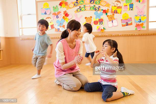 nursery teacher and children playing at day-care center - preschool building stock pictures, royalty-free photos & images