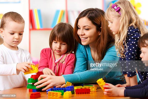 Nursery teacher and preschoolers playing with building blocks
