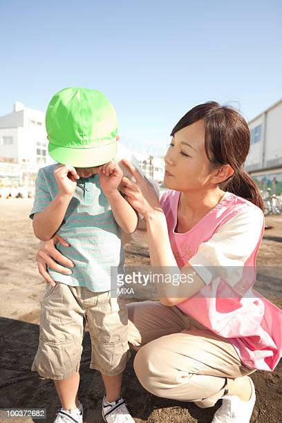 Nursery Teacher Comforting Crying Boy