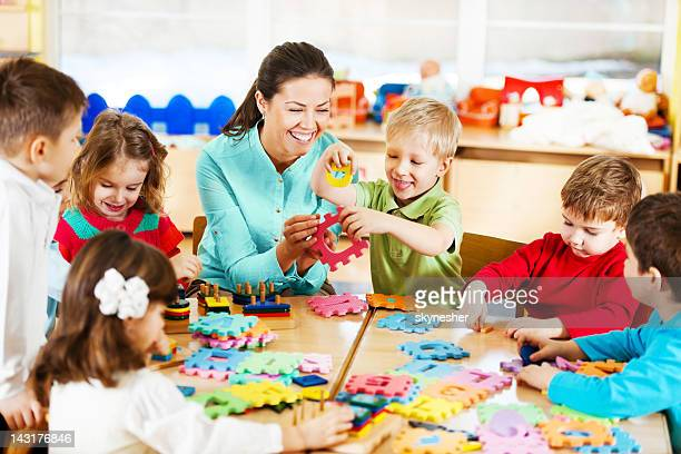 nursery teacher playing with the kids. - middelgrote groep mensen stockfoto's en -beelden