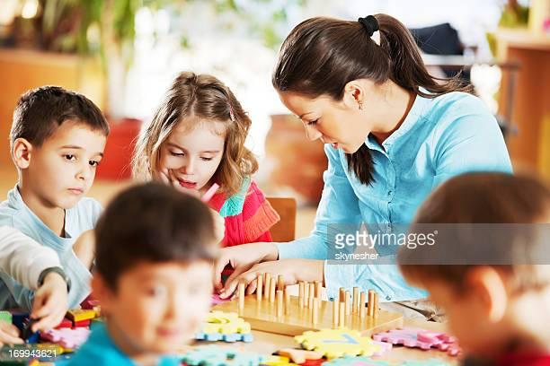 Nursery teacher playing with the kids