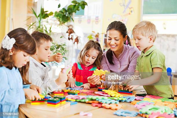 nursery teacher playing with the kids. - preschool building stock pictures, royalty-free photos & images