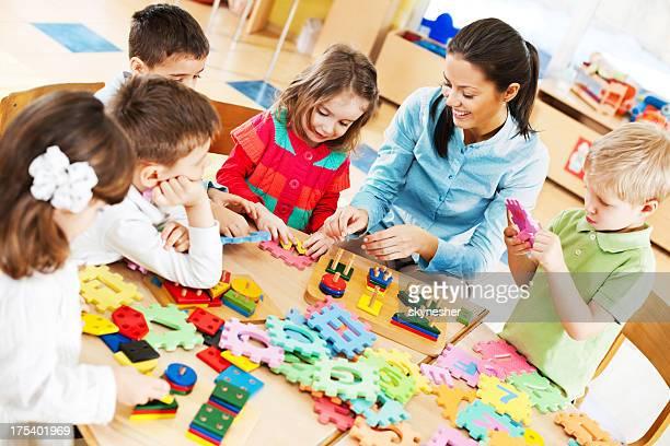 Nursery professor jogando com as crianças.