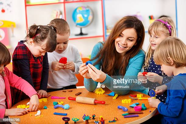 nursery teacher playing with the kids - preschool building stock pictures, royalty-free photos & images