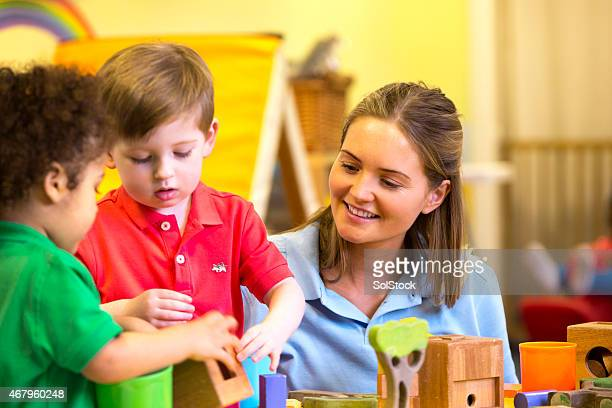 Nursery teacher supervising children playing with building blocks
