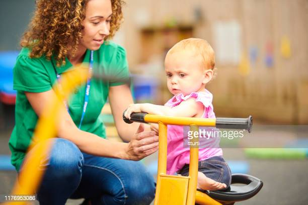 nursery worker with child in playground - preschool stock pictures, royalty-free photos & images