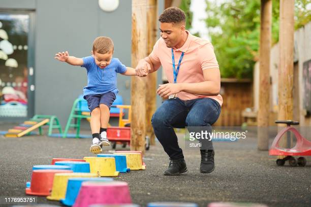 nursery worker with child in playground - britain playgrounds stock pictures, royalty-free photos & images