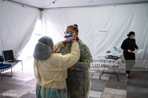 Nurses adjust protective masks inside a testing tent at St Barnabas hospital on March 20 2020 in New York City St Barnabas hospital in the Bronx...