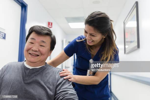 nurse's aide laughs with mature male patient in wheelchair - nursing assistant stock pictures, royalty-free photos & images