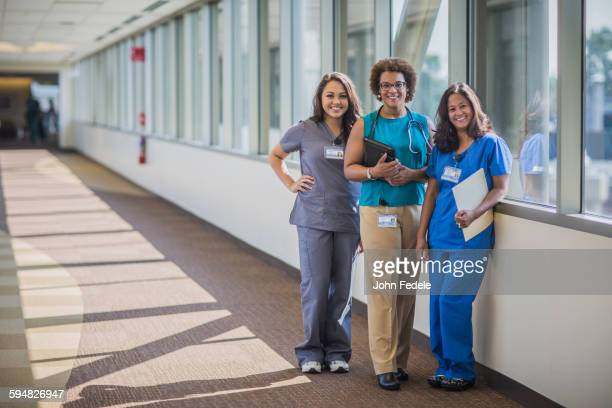 Nurses and doctor smiling in hospital hallway