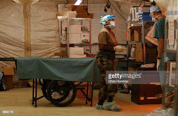 Nurses and doctors briefly exit an operating room where an operation for a detainee is taking place at Camp XRay February 7 2002 in Guantanamo Bay...