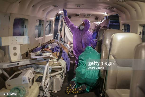 Nurses and doctors prepare to receive a woman in critical conditions after being infected by coronavirus from the airplane that took her from...